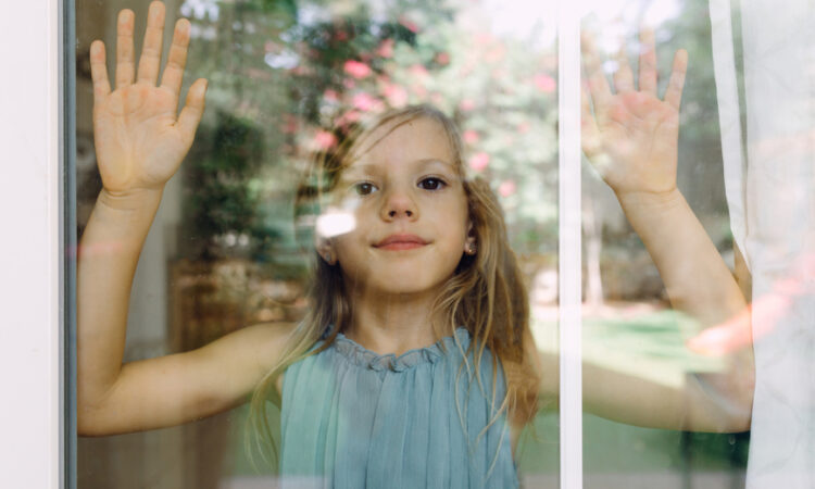 Portrait of a girl looking through the window and pressing her hands against the window glass